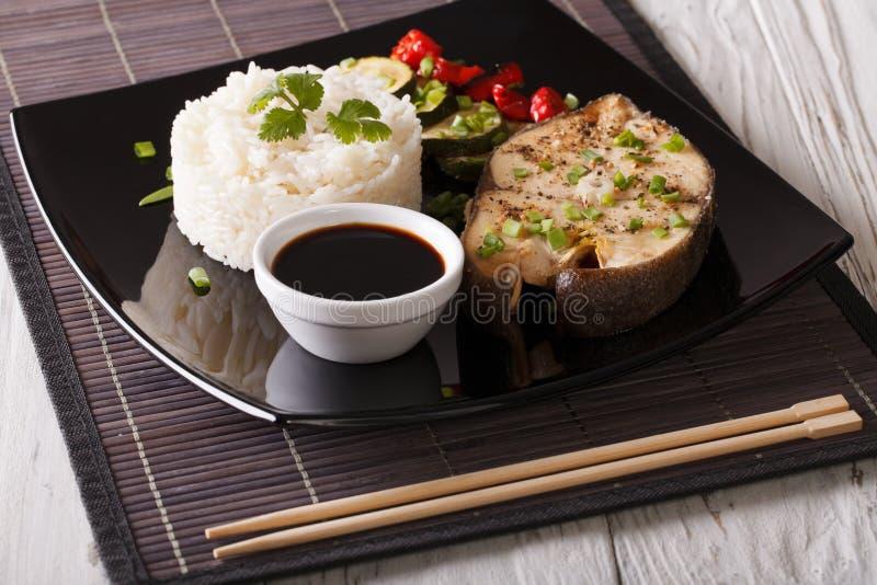 Gebakken vissen, rijst, groenten en sojasaus op een plaatclose-up stock afbeeldingen