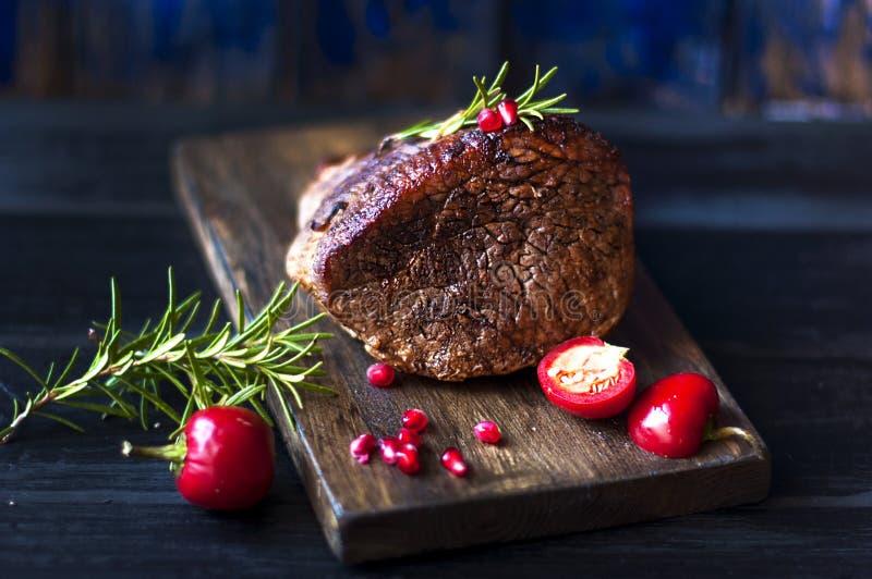 Gebakken vlees met rozemarijn en Spaanse peper Lapje vlees rundvlees diner voor mensen Donkere foto Zwarte achtergrond Houten raa royalty-vrije stock afbeelding