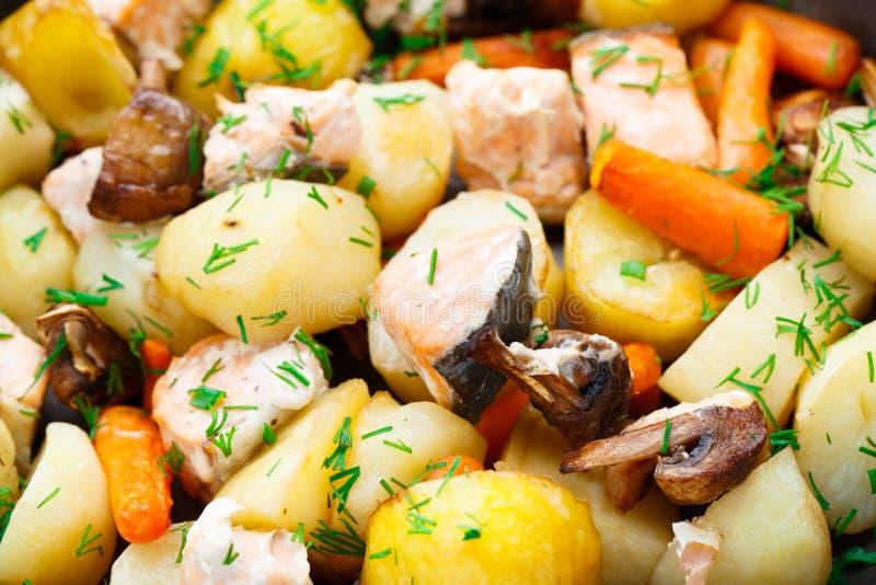 Gebakken zalm met aardappel, paddestoelen en wortel stock fotografie