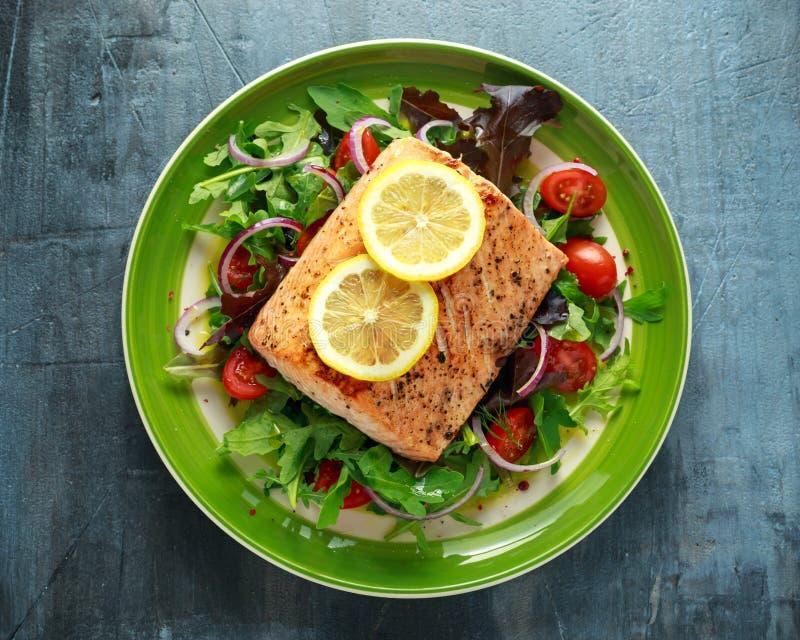 Gebakken zalmlapje vlees met tomaat, ui, mengeling van groene bladerensalade in een plaat Gezond voedsel royalty-vrije stock foto's