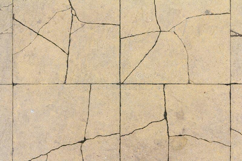 Gebarsten betontegeltextuur De barstachtergrond van de stadsbestrating Het abstracte patroon van de steenbaksteen De textuur van  stock afbeeldingen
