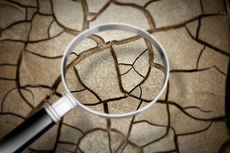 Gebarsten die grond door een vergrootglas - de gevolgen wordt gezien van droogte - Conceptenbeeld royalty-vrije stock afbeelding