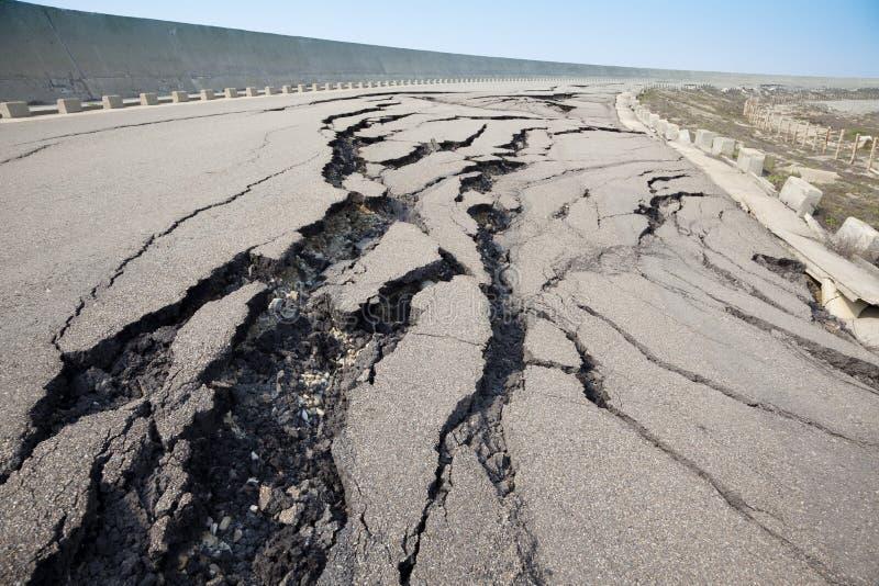Gebarsten weg na aardbeving stock afbeeldingen