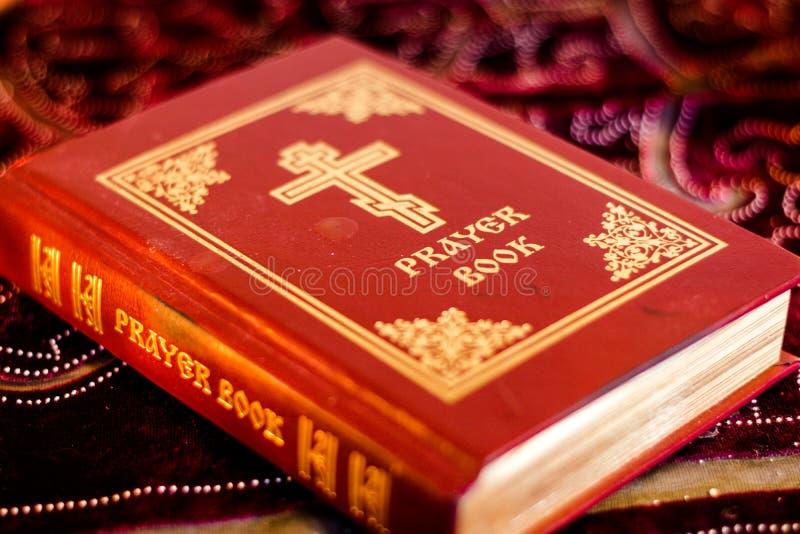 Gebedboek met Orthodox Kruis op lijst met zacht trillend kaarslicht stock fotografie