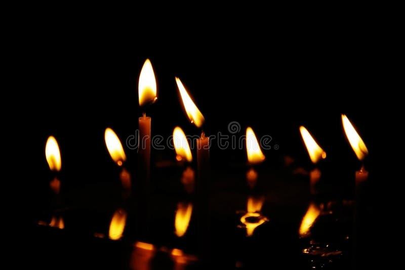 Gebedkaarsen die in stille die duisternis van tempel branden, in water wordt weerspiegeld stock foto's