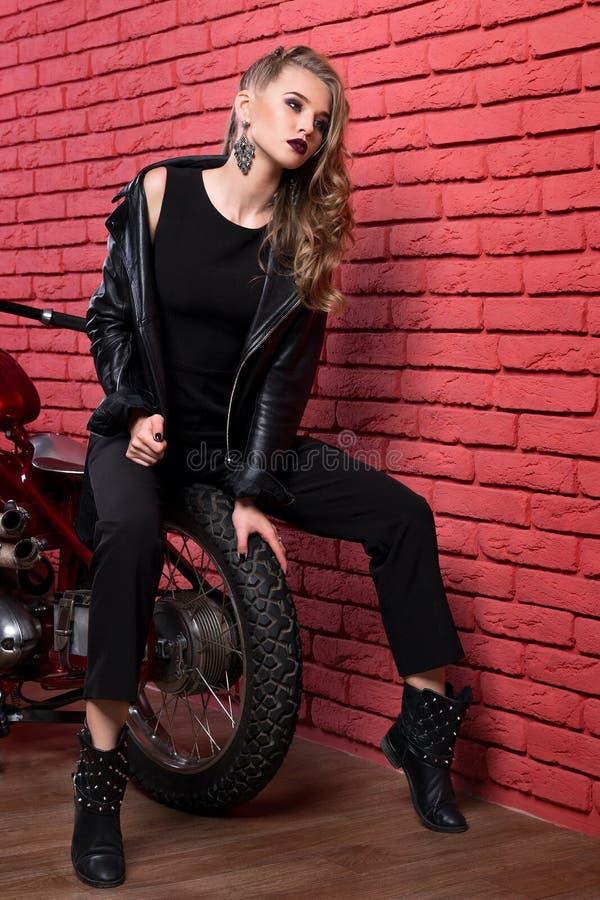 Gebegeerd vrouw of meisje in een leerjasje en een strakke broek, laarzen stock foto's