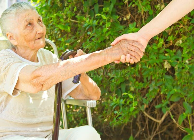 Geben einer Handreichung für eine alte Dame des Sitzens im Park lizenzfreies stockbild