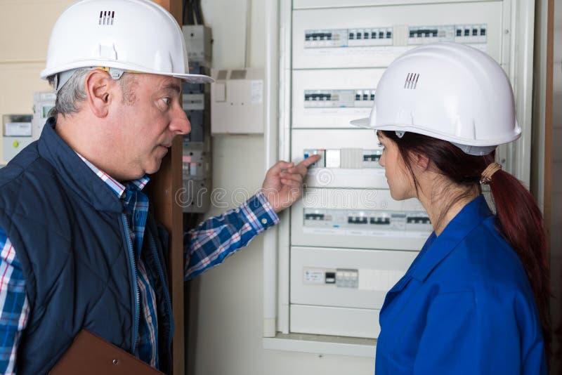 Geben Sie den Elektriker in die Lehre, der fusebox mit älterer Arbeitskraft betrachtet stockfoto