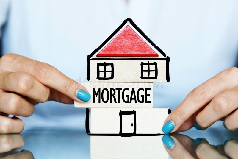 Geben Sie die Hypothek des Eigentumskonzeptes mit junger Frau frei und bringen Sie Symbol auf einer Tabelle unter stockfoto