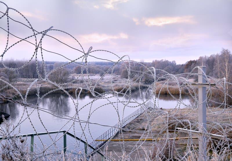 Geben Sie einen Zaun des Stacheldrahts im Winter im Frost an der Dämmerung bekannt lizenzfreies stockbild