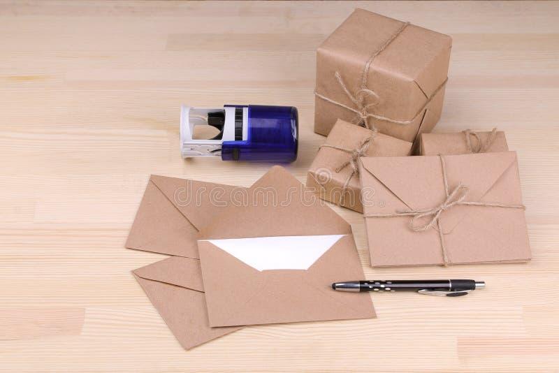 Geben Sie Umschläge und Pakete, Stempel und Briefkopf mit einem Griff auf einem Holztisch bekannt Post- oder Lieferungskonzept lizenzfreies stockbild