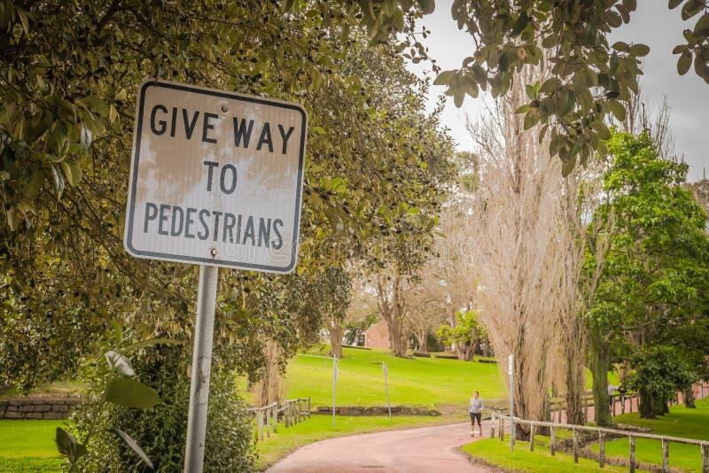 Geben Sie zum Fußgängerzeichen nach, das im Park zeigt lizenzfreie stockfotos