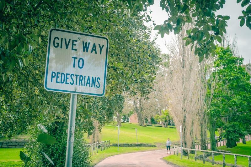 Geben Sie zum Fußgängerzeichen nach, das im Park zeigt stockbilder