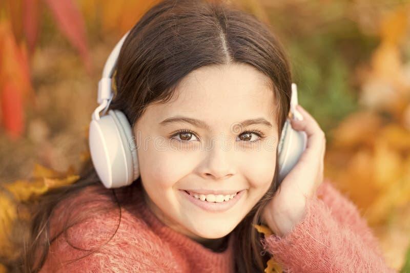 Geben Sie zur Nut nach Gl?ckliche Kinderabnutzungskopfh?rer Wenig Musikfan am Herbsttag Gl?ckliches kleines M?dchen im Herbst wen stockbild