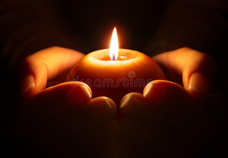 Gebet - Kerze in den Händen stockfoto