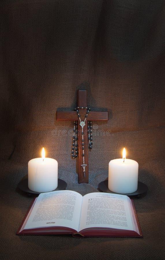 Gebets-Buch, Rosenbeet, Kruzifix und zwei Kerzen lizenzfreie stockfotos