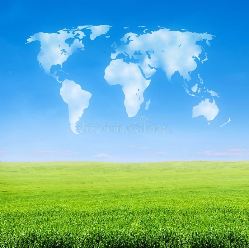 Gebied van gras met wereld gevormde wolken royalty-vrije stock afbeelding