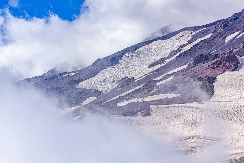 gebieden van gletsjers en berghellingen met wolken en mist worden behandeld die royalty-vrije stock fotografie