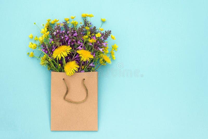 Gebieds kleurrijke rustieke bloemen in ambachtpakket op blauwe achtergrond De Vlakte van de groetkaart legt lente van Hello van h royalty-vrije stock afbeeldingen