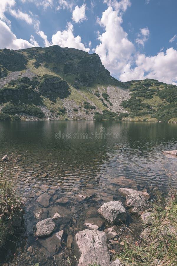 Gebirgs-See-Panoramaansicht in Spätsommer in slowakischem Karpaten-Tatra mit Reflexionen von Felshügeln im Wasser Rohacske-plesa stockfotos