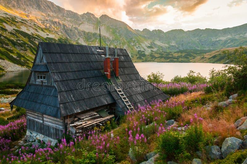 Gebirgshütte in der Mitte eines Gebirgstales lizenzfreie stockfotos