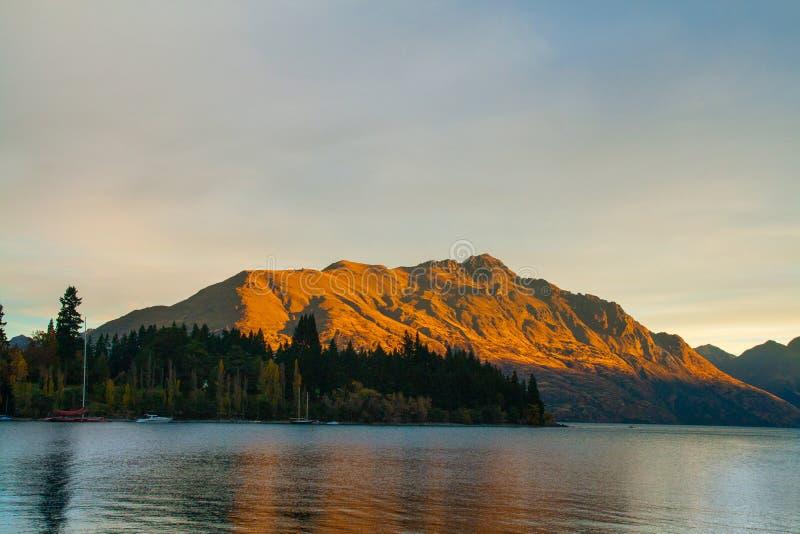Gebirgsherbstlandschaft gefärbt durch goldene Reflexion der untergehenden Sonne, Cecil Peak Queenstown-Markstein lizenzfreie stockbilder