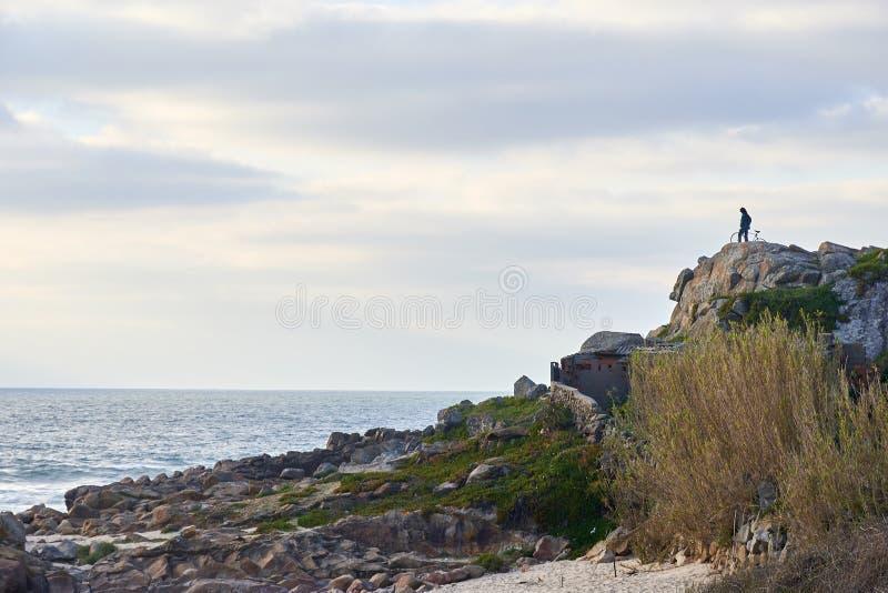 Gebirgsradfahrer beobachtet das Meer von der Spitze der Klippe stockbild