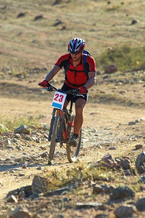 Gebirgsradfahrer, der in der Wüste läuft stockbilder
