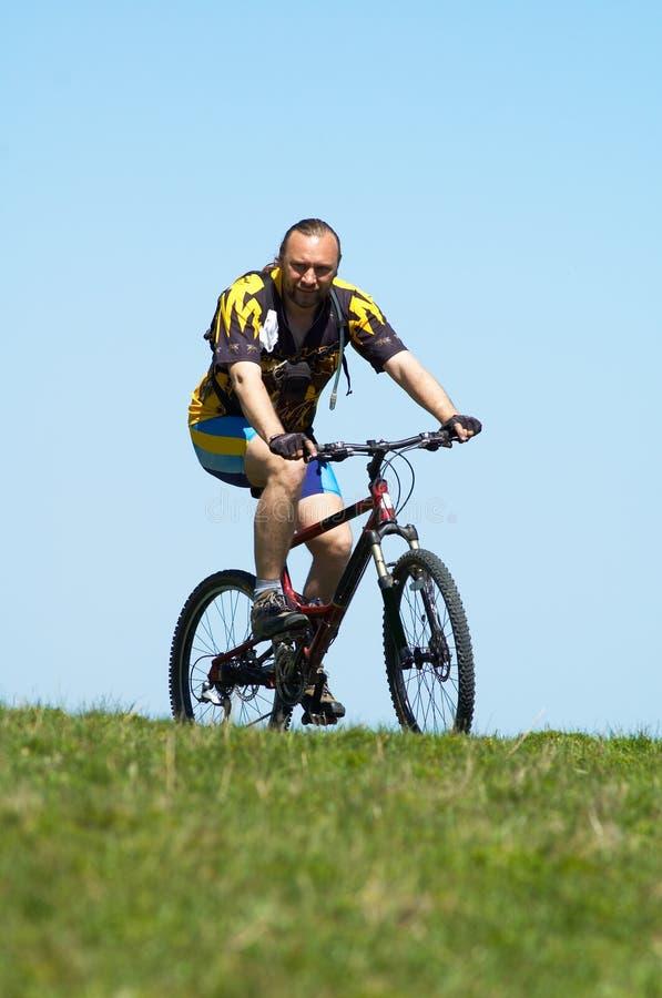 Gebirgsradfahrer, -himmel und -gras lizenzfreie stockbilder