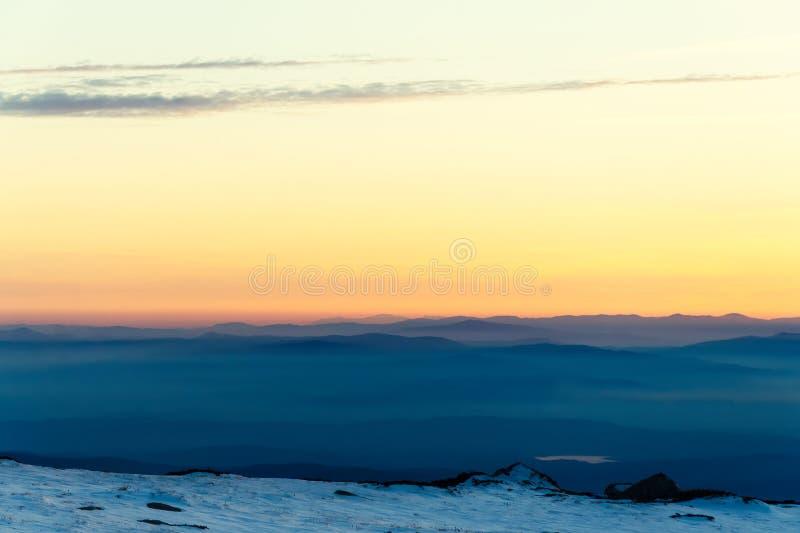 Gebirgsschichten und bunter Sonnenuntergang im winterlichen Berg lizenzfreie stockfotografie