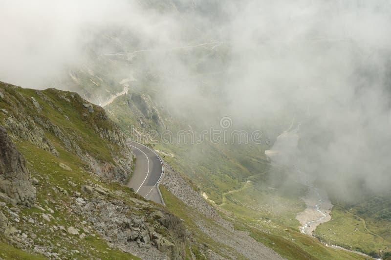 Gebirgsstraße in den Wolken in den Alpen in der Schweiz lizenzfreie stockfotos