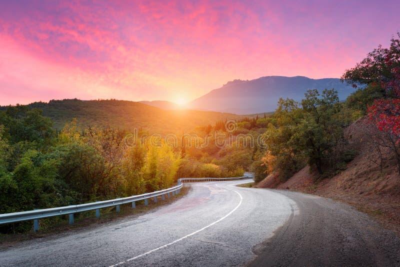 Gebirgsstraße, die durch den Wald mit drastischem buntem Himmel und roten Wolken bei buntem Sonnenuntergang im Sommer überschreit stockfotografie