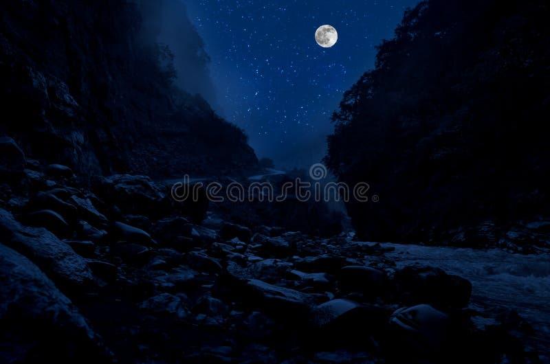 Gebirgsstraße durch den Wald auf einer Vollmondnacht Szenische Nachtlandschaft des dunkelblauen Himmels mit Mond azerbaijan stockbilder