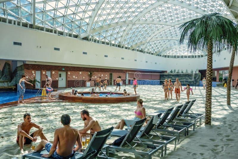 Gebirgsstrand-Wasser-Park erlaubt Leuten, eine Winterreise in den heißen Sommer zu machen lizenzfreie stockfotos