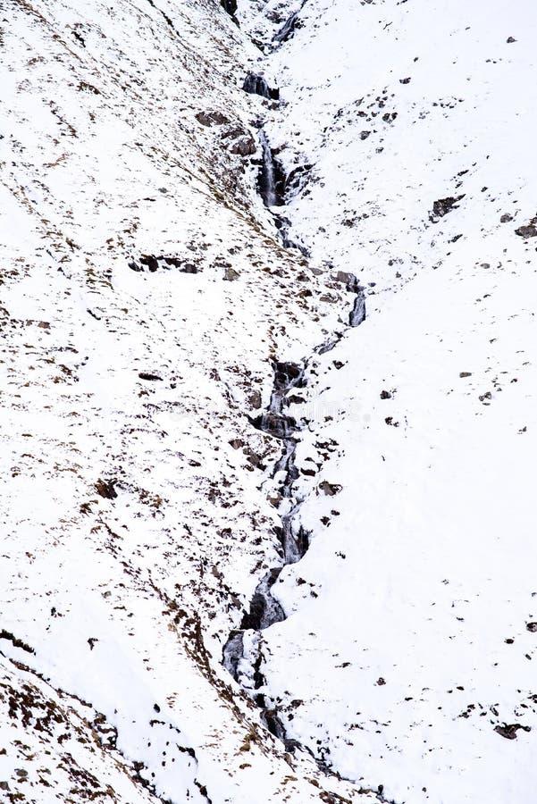 Gebirgsstrom durch Schnee stockfotos