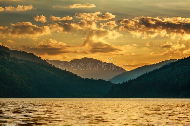 Gebirgswaldsee auf drastischem Sonnenunterganghimmel des Hintergrundes lizenzfreie stockfotografie