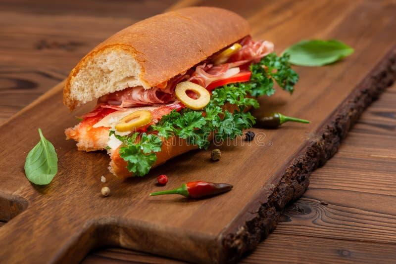 gebissen weg vom Sandwich mit Gemüse, verzierten Gewürze und Schinken Grüns auf dunklem Schnittschreibtisch lizenzfreie stockfotos