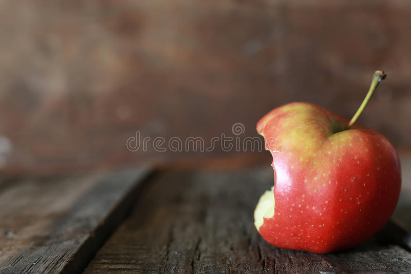 Gebissener Apfel auf einem hölzernen Hintergrund lizenzfreie stockbilder