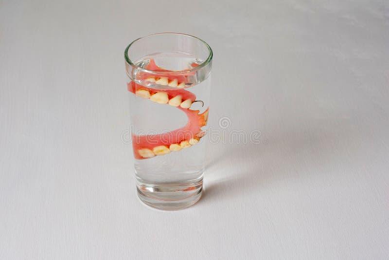Gebit in een glas met water op een witte achtergrond royalty-vrije stock foto's
