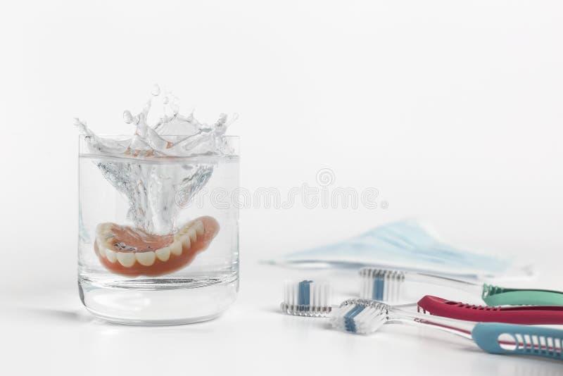 Gebittenconcept met glas, masker en tandenborstel stock fotografie