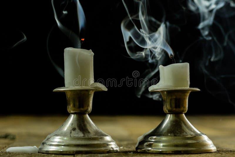Geblasene Kerzen in den silbernen Kerzenständern mit geräuchertem Docht Rauch für stockfotos