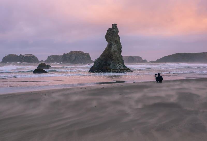 Geblasener Sand des Winds auf Strand bei Sonnenuntergang stockbild