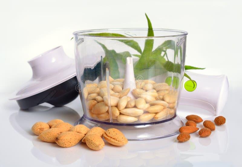 Geblichene Mandeln in einer Mischmaschine mit ungeschälten Nüssen Auf Weißrückseite lizenzfreie stockfotos
