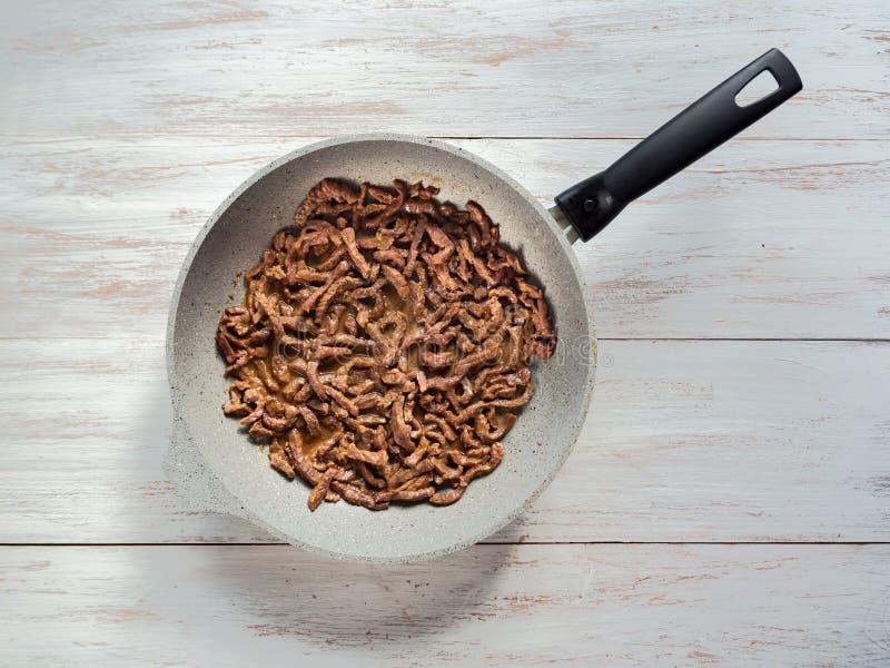Geblichenes Fleisch in einer Bratpfanne auf einem Holztisch stockbilder