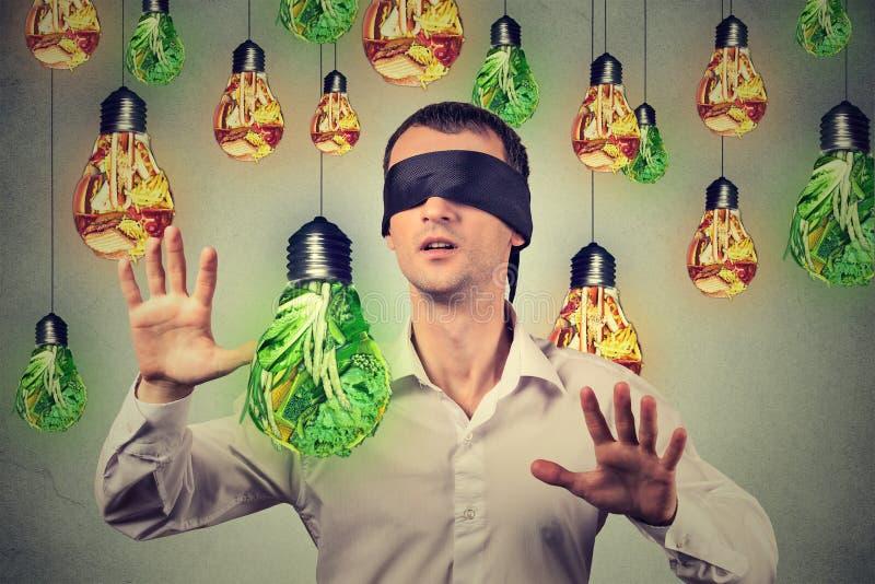 Geblinddochte mens die die door gloeilampen lopen als ongezonde kost groene groenten worden gevormd stock foto's