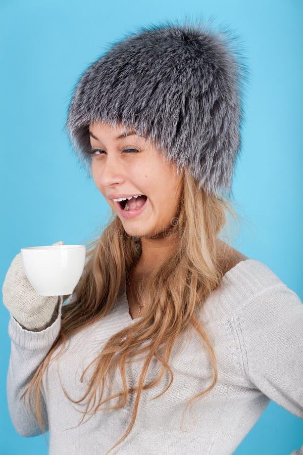 Geblinzelte Frau, die ein Cup mit heißen Getränken anhält lizenzfreie stockbilder