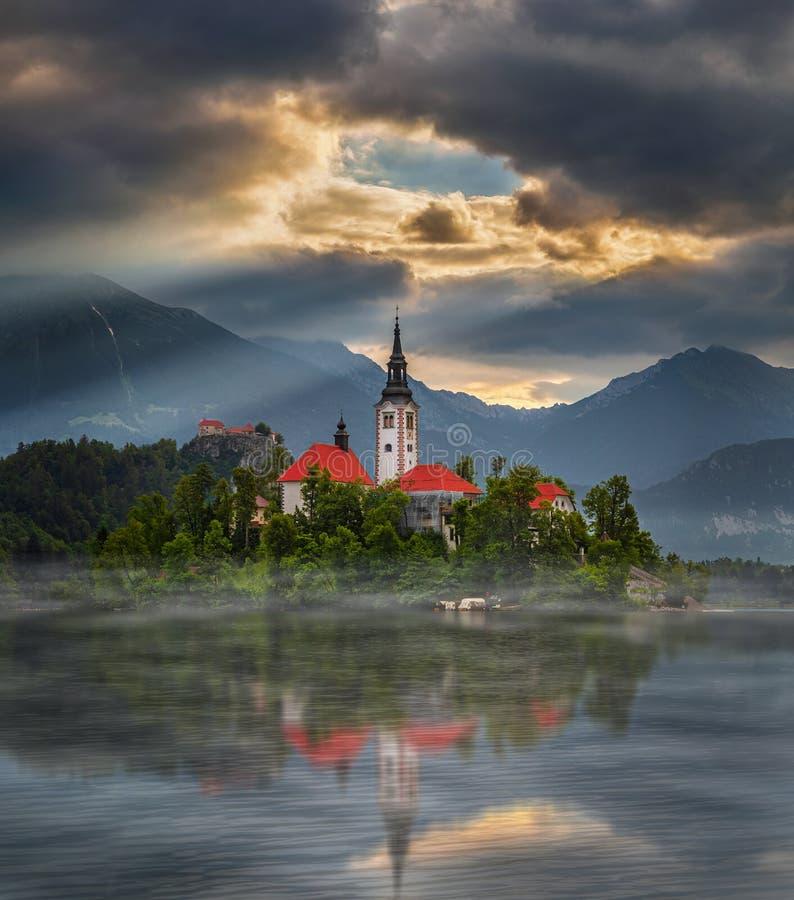 Geblutet, Slowenien - nebelhafter Sonnenaufgang bei See ausgeblutetem Blejsko Jezero mit der Pilgerfahrt-Kirche der Annahme von M stockfotografie