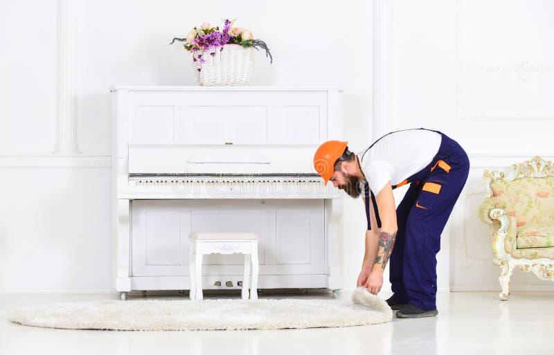 Gebogen arbeider die een tapijt rollen Mens die met tatoegering op wapen witte deken verwijderen uit ruimte Het concept van de hu stock foto's