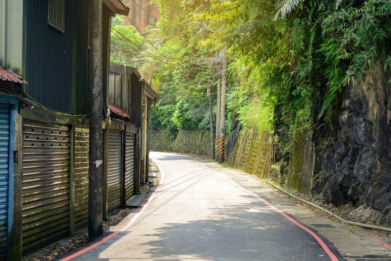 Gebogen asfaltweg in een landelijk dorp met een zonneschijn in de ochtend, Wulai, Taiwan royalty-vrije stock foto