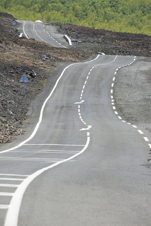 Gebogen asfaltweg over vulkanische lava, Bijeenkomsteiland, Frankrijk stock foto's
